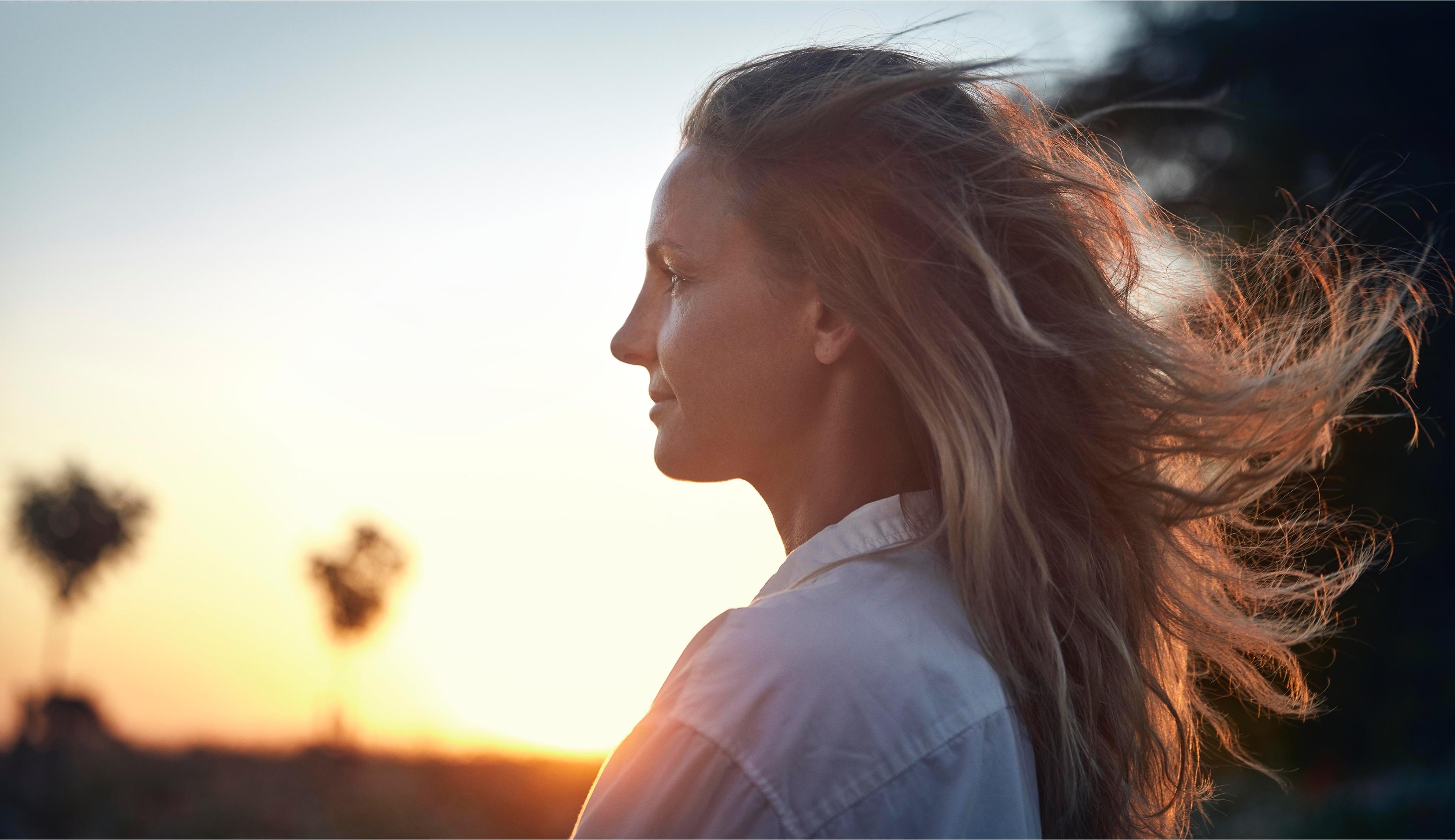Närbild kvinna med långt hår i solnedgången